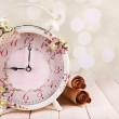 Beautiful vintage alarm clock with flowers on light background — Stock Photo #49767221