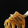 Italian pasta spaghetti on fork on black background — Stock Photo #49769307