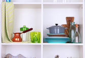 Kitchen utensils and tableware on beautiful white shelves — Stockfoto