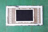 Wooden frame with blank old photo on wooden background — Стоковое фото