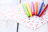 Bright markers with paper on wooden table close-up — Stock Photo