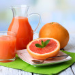 Half of grapefruit, glass jug with fresh juice and spoon on plate on light background — Stock Photo #49773569