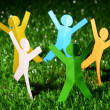 Paper people on green grass, close up — Stock Photo #49774165