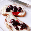 Fresh bread with cherry jam and homemade butter on plate on wooden background — Stockfoto #49775059