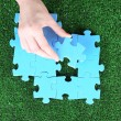 Hand holding puzzle piece on green grass background — Stock Photo #49776303