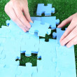 Hand holding puzzle piece on green grass background — Stock Photo #49776305