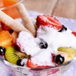Fresh fruits salad with ice cream in bowl and juice on wooden background — Stock Photo