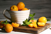 Ripe apricots with green mint leaves on cutting board, on wooden background — Stock Photo