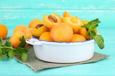 Ripe apricots with green mint leaves in bowl on color wooden background — Stock Photo