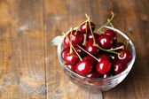 Cherries in color bowl on wooden background — Stock Photo