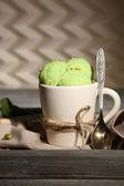 Sabroso helado de pistacho en la taza en la mesa de madera — Foto de Stock