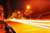 Moving car with blur light through city at night — Stockfoto
