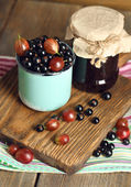 Ripe blackcurrants and gooseberries in mug and glass jar with tasty jam on board, on wooden background. — Zdjęcie stockowe