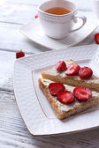Fresh toast with  homemade butter and fresh strawberry on plate on wooden background — Stock Photo