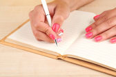 Female hand with stylish colorful nails holding pen, on wooden table background — Stock Photo