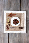 Wooden frame with white mug, coffee grains and spices on wooden background — Stock Photo