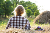Beautiful girl sitting on haystack in field — Stock Photo