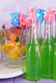 Bottles with drink and sweets on table on bright background — Stock Photo