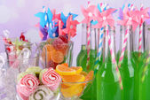 Bottles with drink and sweets on bright background — Stock Photo