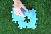 Hand holding puzzle piece on green grass background — Stock Photo