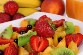 Fresh fruits salad on plate with berries and juice close up — Foto Stock