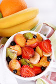 Fresh fruits salad in bowl on napkin close up — Stock Photo
