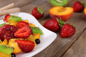 Fresh fruits salad with ice cream on plate and berries on wooden background — Foto Stock