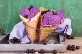 Tasty ice cream with berries in waffle cones on green wooden background — Stock Photo