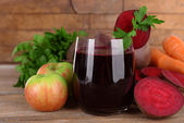 Glass of fresh beet juice and vegetables on wooden background — Stock Photo
