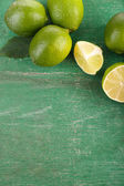 Fresh juicy limes on old wooden table — Stock Photo