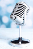 Vintage microphone on table on light blue background — Stock Photo