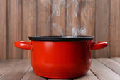 Cooking pot with steam on table on wooden background — Stock Photo