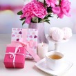 Composition of beautiful peonies in vase, tea in cup and marshmallow, on table, on light background — Stock Photo #49820775