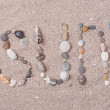 Word sun made from sea shells and stones on sand — Stock Photo #49823199