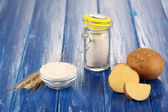 Starch in bowl and bank on wooden table close-up — Stock Photo