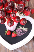 Strawberry in chocolate on skewers — Stock Photo