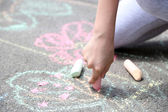 Girl drawing with chalk on asphalt — Stock Photo