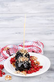 Sweet caramel apples on sticks with berries, on wooden table — Stockfoto