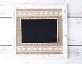 Wooden frame with blank old photo on wooden background — Stock Photo