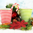 Cups of hot cacao with chocolates and Christmas decorations on table on bright background — Stock Photo #49844581