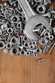 Wrench on bolts, screws and nuts on wooden table — Stock Photo