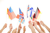 Hands holding different flags — Stock Photo