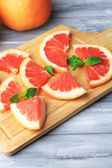 Reife grapefruits auf schneidebrett auf holztisch, auf hellem hintergrund — Stockfoto