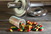 Dumbbell and colorful pills — Stock Photo
