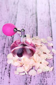 Perfume bottle with petals — Stock Photo