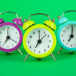 Colorful alarm clock on green background — Stock Photo #49877185
