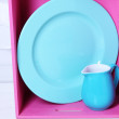 Beautiful  bright shelves and boxes with tableware  on  light wall background — Stock Photo #49877931