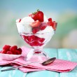 Creamy ice cream with raspberries on plate in glass bowl, on color wooden table, on bright background — Stock Photo #49880459