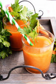 Glasses of carrot juice with fresh carrots and parsley on wooden tray close up — Stock Photo