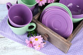 Bright dishes with flowers in crate on table close up — Stock Photo